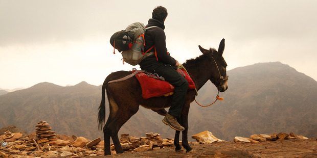 Jordan Trail cartographer Amjad Shahrour sits atop a donkey on the footpath between Little Petra and the famous monastery in Petra southern Jordan. Photo / AP