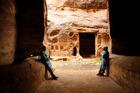 Jordan Trail cartographer Amjad Shahrour, left, and Petra-based guide Mahmoud Badoul keep dry during heavy rains at Little Petra. Photo / AP