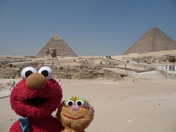 Elmo and friend pose in front The Pyramids at Giza. Phtoo / Susan Gutmann