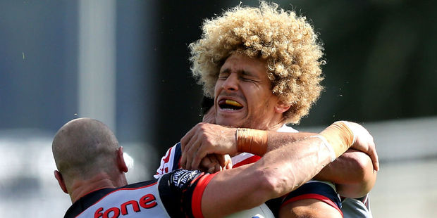 Roosters forward Eloni Vunakece and his magnificent head of hair is tackled by the Warriors defence. Photo / Getty