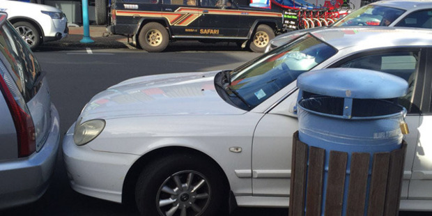 The badly-parked sedan is squeezed into a parallel spot on a busy road just inches away from the car in front of it. Photo / Supplied