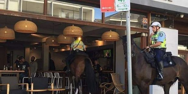 A bizarre photo has surfaced of a mounted police officer riding a horse (centre) into the Beach Road Hotel in Bondi, Sydney. Photo: Jonno Seidler and Carmen Culina