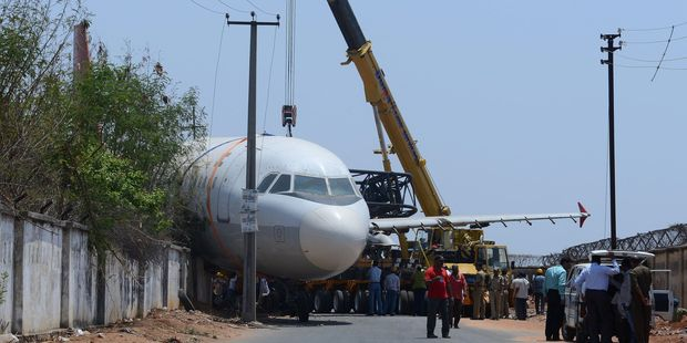 Loading Indian police and rescue officials gather in front of an Air India passenger plane which fell from a ground transporter. Photo / Getty Images