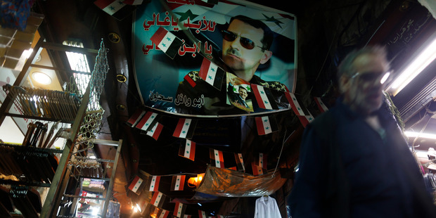 A Syrian walks under a poster of the Syrian President Bashar Assad at the popular Hamidiyeh old market in Damascus. Photo / AP