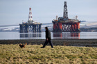 In this Feb 15 photo, a man walks past oil platforms laid-up in the Cromarty Firth near Invergordon in the Highlands of Scotland. Photo / AP