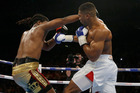 US boxer Charles Martin, left, is knocked down by British boxer Anthony Joshua during their IBF heavyweight title bout at the O2 Arena in London. Photo / AP.