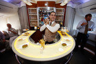 Cabin crew member Troy Whittle in the Business Class lounge bar aboard an Emirates A380. The airline's customers drank 11.4m bottles of wine last year. File photo / Greg Bowker.