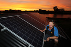 BRIGHT TIME: Solar power specialist Aaron Duncan with the vital components - the panels and the sun. PHOTO/DUNCAN BROWN