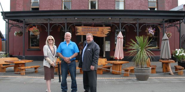 Bayleys saleswoman Toni Sinclair, left, Buckhorn Bar and Grill owner JK Kennedy, centre, and Bayleys' salesman Dave Wish outside Buckhorn in Carterton.  PHOTO/EMILY NORMAN