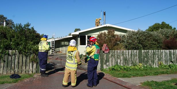 Firefighters extinguishing a house fire in Featherston yesterday. PHOTO/ALISA YONG