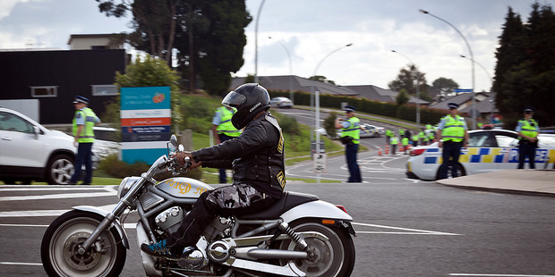 A motorcyclist riding through heavy police presence at Te Paeroa Rd Roundabout in Bethlehem. Photo/Andrew Warner