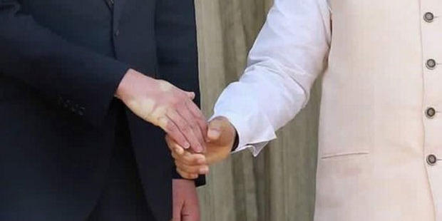 Loading The strong handshake of Narendra Modi leaves its mark on Prince William.