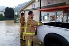 Firefighters assist at a flooded garage in Coromandel township after heavy rain yesterday. Photo / Supplied