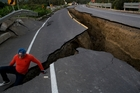 A resident jokes around on a collapsed highway in Chacras, Ecuador. Picture / AP