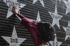 Terrance May, a musician who goes by the name May Millions, takes a moment at a growing memorial outside First Avenue, a Minneapolis club where Prince filmed a large portion of his classic movie Purple Rain and recorded several songs on the accompanying album. Photo / AP