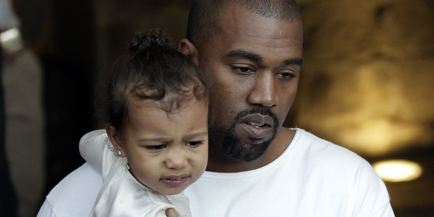 US rapper Kanye West, husband of US reality TV star Kim Kardashian, carries their daughter North. Photo / Getty Images