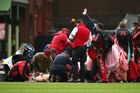A member of the Australian Army Red Beret's receives attention after landing heavily on the SCG. Photo / Getty