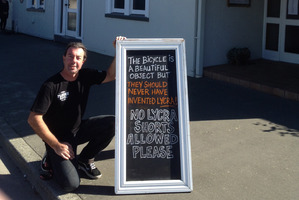 Mike Saunders of The Plough Hotel in Rangiora with his sign banning lycra from the pub.