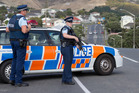 Armed police officers at the cordon on Warspite Avenue in Porirua following the shooting of a police dog. Photo / Mark Mitchell