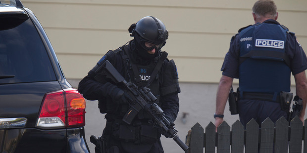 An Armed Offenders Squad member moving into position near the house. Photo / Mark Mitchell