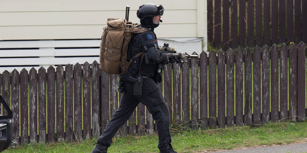 An Armed Offenders Squad member moving into position near where gunman Pita Rangi Te Kira is holed-up in a house on Kokiri Cres in Porirua. Photo / Mark Mitchell