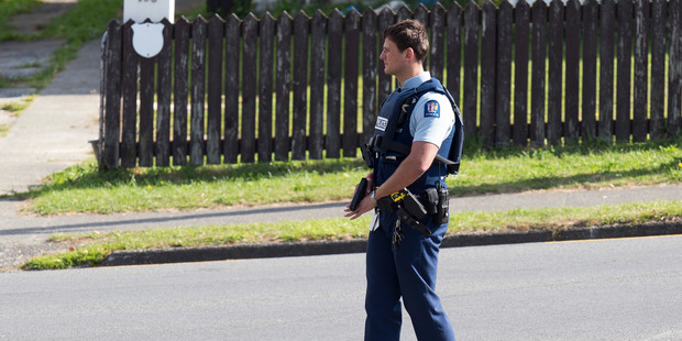 Loading An armed police officer at a cordon on Warspite Avenue near where gunman Pita Rangi Te Kira is holed-up in a house on Kokiri Cres in Porirua. Photo / Mark Mitchell