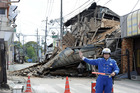 A police officer stands guard in front of a house destroyed by an earthquake in Mashiki, Kumamoto prefecture, southern Japan. Photo / AP