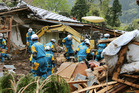 Police officers search for missing persons near houses destroyed by landslide in Minamiaso. Photo / AP