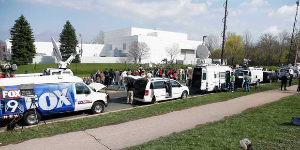 Media satellite trucks and fans line the street outside Paisley Park. Photo / AP