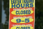 A sign displays Easter trading hours on a shop window. Photo / Brett Phibbs