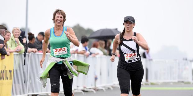 27-year-old Ashleigh Spencer, right, finishes the Tauranga half marathon last Sunday.