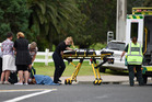 People gather to help a cyclist involved in a crash with a car at Mount Maunganui. Photo/George Novak