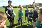 Magpie Ellery Wilson working with a group of kids at a holiday event run by Hawke's Bay Rugby. Photo / Duncan Brown