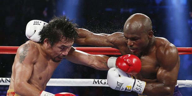 Manny Pacquiao, left, tries to avoid a punch by Timothy Bradley during their WBO welterweight title bout. Photo / AP