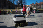 Schoolchildren watch a prototype delivery robot, developed by Starship Technologies, pass in the city center of Tallinn, Estonia. Photo / Peti Kollanyi