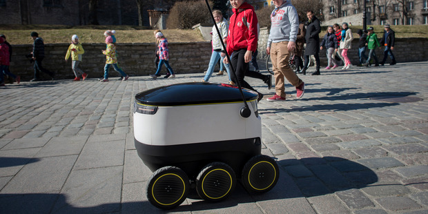 Schoolchildren watch a prototype delivery robot, developed by Starship Technologies, pass in the city center of Tallinn, Estonia. Photo / Peti Kollanyi