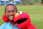 A Fijian boy shows his delight while hanging out with Elmo. Photo / Corinne Ambler/IFRC