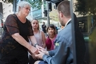 Chris Austin (left) along with grand children, L-R Tiffany Peace, 10 and Xanthee Austin, 8, talk to a homeless man on Auckland's Queen street. 20 April 2016. New Zealand Herald photograph by Nick Reed