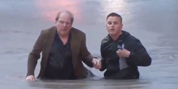 The reporter waded into the chest-deep water and helped the man struggle toward safety. Photo / YouTube