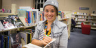 Rhi Munro holds a copy of the book Maori Myths and Legends. The book was checked out of Epsom Library on the 17th of December 1948 and returned to the library today. Photo / Michael Craig