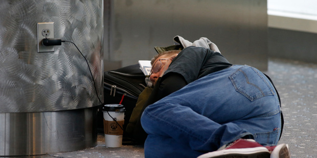 A traveller sleeps at Denver International Airport. A French think-tank believes naps at work are good for business. Photo / AP