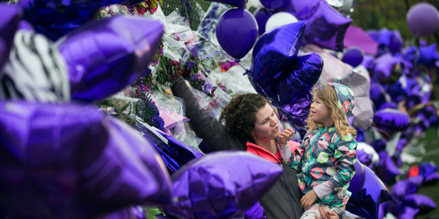 Joy Meuleners holds her niece Keira Abeln at a memorial for Prince at Paisley Park in Chanhassen. Photo / AP