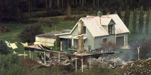Seascape Cottage, where Martin Bryant held several people hostage, smolder on April 29, 1996 near Port Arthur, Australia. Photo / AP