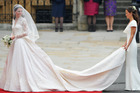 Catherine Middleton waves to the crowds as her sister and Maid of Honour Pippa Middleton holds her dress. Photo / Getty
