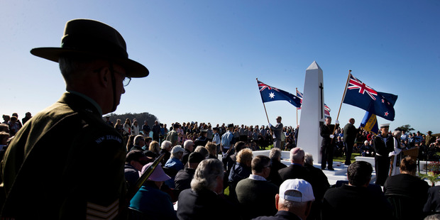 Loading The New Zealand and Australian flags fly proudly at the cenotaph in Mt Maunganui for the mid-morning service. Photo / Alan Gibson