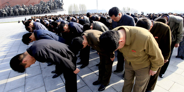 People bow in front of bronze statues of North Korea's late leaders Kim Il Sung and Kim Jong Il at Mansu Hill in Pyongyang. Photo / AP