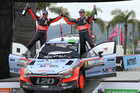Hyundai Motorsports driver Hayden Paddon, right, and co-driver John Kennard, both from New Zealand, celebrate in the podium. Photo / AP.