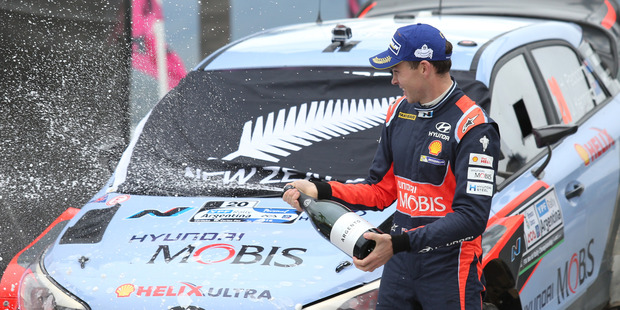 Hyundai Motorsports driver Hayden Paddon from New Zealand, celebrates in the podium after winning the fourth round of the FIA World Rally Championship. Photo / AP.