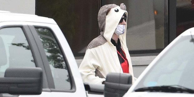 A man wearing a full animal costume and surgical mask walks out of a TV station in Baltimore. Photo / AP