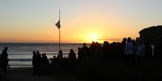 People in Whangamata gather to commemorate Anzac Day with a flag flying half mast as the sun rises. Photo/Lesley Staniland